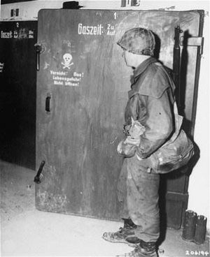 """Dachau """"gas chamber"""" door. This official US Army photo was taken at Dachau on April 30, 1945, one day after the camp's liberation. It shows a GI standing in front of a door marked with a skull and crossbones. According to the official caption, """"these chambers were used by the Nazi guards for killing prisoners of the infamous Dachau concentration camp."""" In fact, this is a small disinfection gas chamber used for delousing clothes, as part of the routine to curtail the spread of disease. This chamber was never used to kill people. For several decades, this photo has been widely reproduced to help keep alive the notorious Dachau """"gas chamber"""" myth. A large blow-up of this photograph was on display at the Weber-Shermer debate."""
