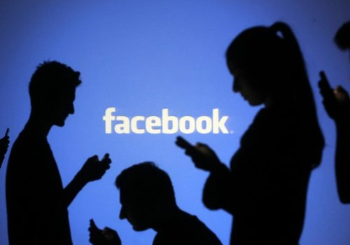 People pose with mobile devices in front of projection of Facebook logo in this picture illustration taken in Zenica