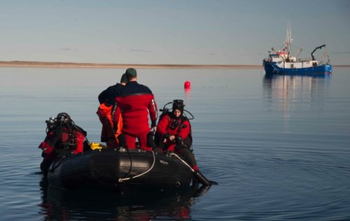 Parks Canada's underwater archeology team prepares to enter the water on a dive to the wreckage of HMS Erebus in 2015, while being supported by the Arctic Research Foundation's vessel the Martin Bergmann. The same vessel located HMS Terror after detouring to Terror Bay on the advice of an Inuit crew member.