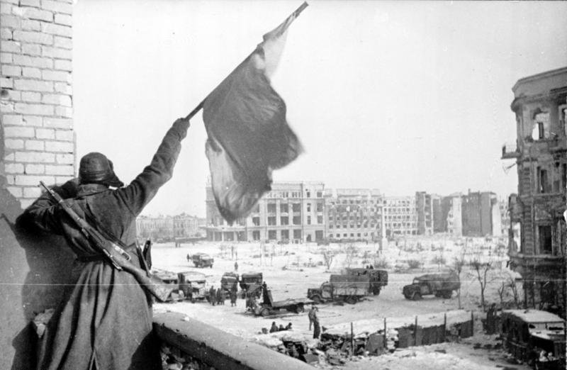 Soviet soldier waving the Red banner over the central plaza of Stalingrad