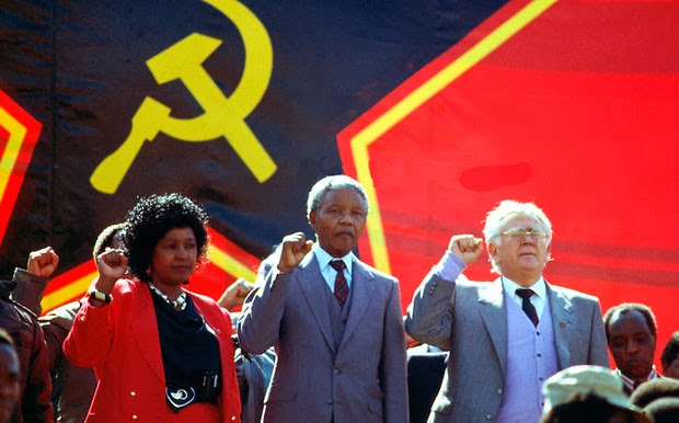 https://nationalvanguard.org/wp-content/uploads/2015/08/Winnie_Mandela_Nelson_Mandela_Yossel_Joe_Slovo_hammer_and_sickle_red_star_flag_banner.jpg