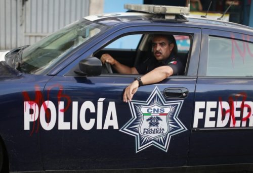 Federal police sits inside a police vehicle which was spray-painted by demonstrators, during a demonstration to demand justice for the disappearance of the 43 trainee teachers, in Chilpancingo