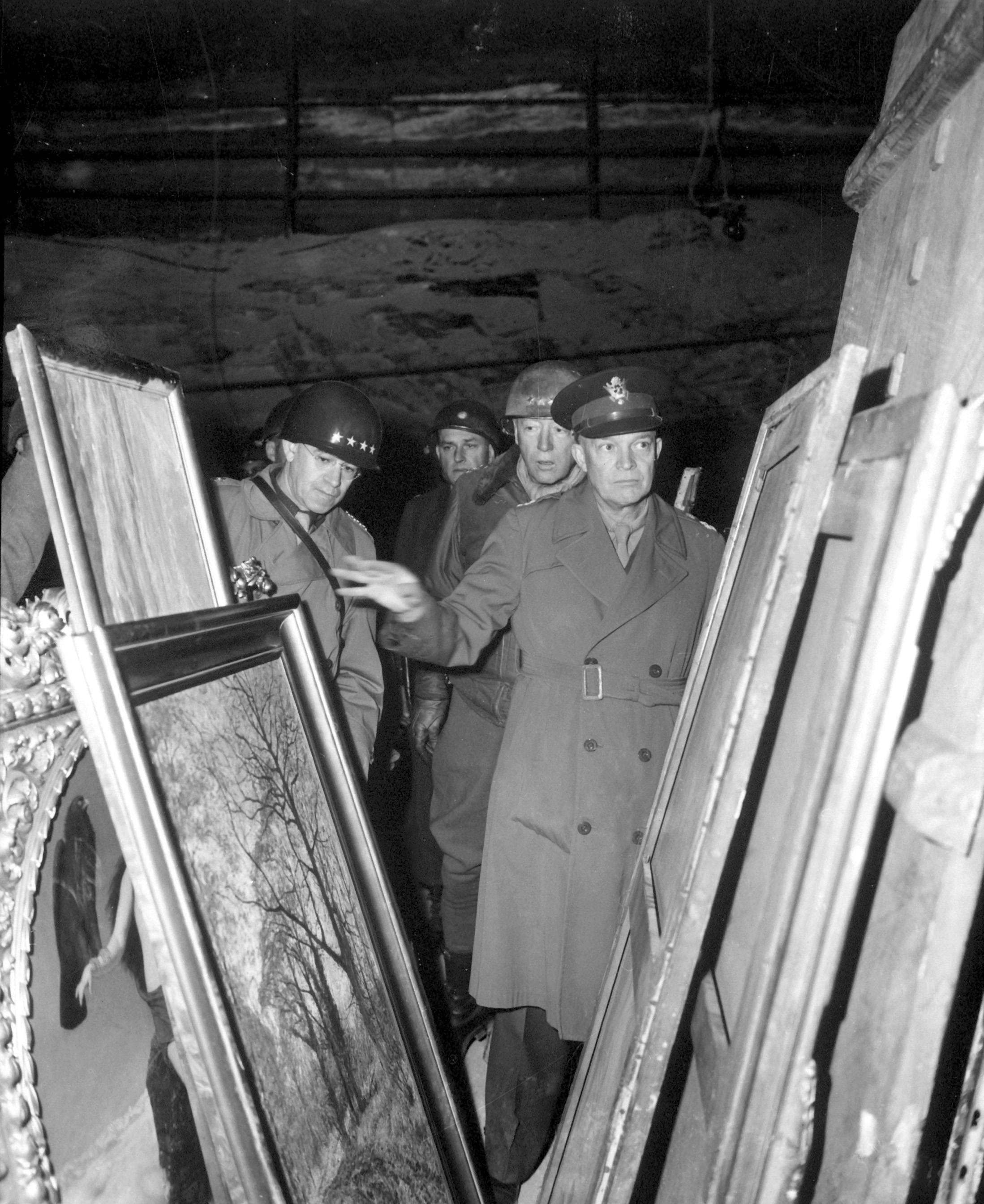 U.S General Dwight D. Eisenhower, Supreme Allied Commander, accompanied by General Omar N. Bradley and Lieutenant General George S. Patton, Jr., inspects art treasures secured from Allied air attacks by their being hidden in a salt mine in Germany. These artworks were looted and shipped to the United States where many are still illegally stored.